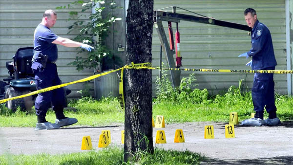 Maine State Police detectives mark evidence in the driveway at a mobile home at 24 Main Street in Detroit after a deceased male was found early Thursday.