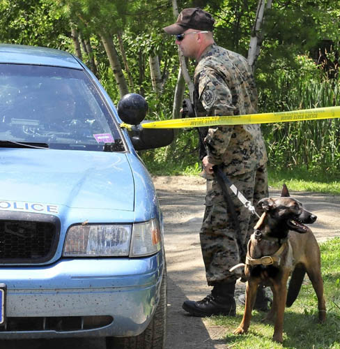 A state police trooper and dog prepare to search the grounds of a mobile home at 24 Main Street in Detroit after a deceased male was found earlier Thursday.
