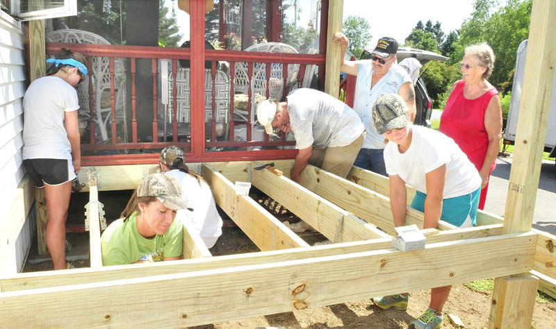 North Anson residents Robert and Carrol Thompson, at right, watch as the group Mission of the Eastward builds a porch on their home on Tuesday. From left, Lauren Kane, Emily Kelley, Allie Hoffman, Dennis Painter and Lauren Logan work on the structure.