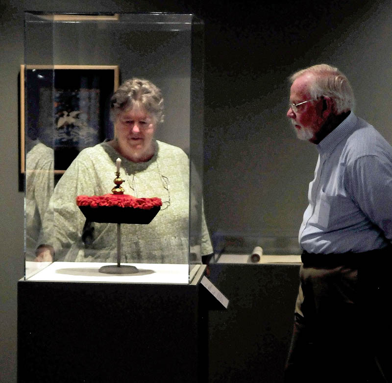 "Faye and Jim Nicholson look over the ""Winter Court Hat"" on display at the Colby College Museum of Art."
