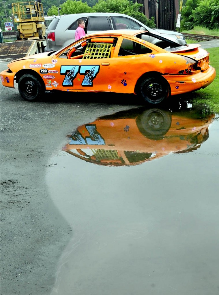 "A race car is parked in a large puddle near Fort Halifax Park in Winslow on a wet Tuesday. The car is part of the Winslow Family 4th of July's ""Total Truck Experience,"" where kids get a chance to see, up-close, municipal and commercial trucks."