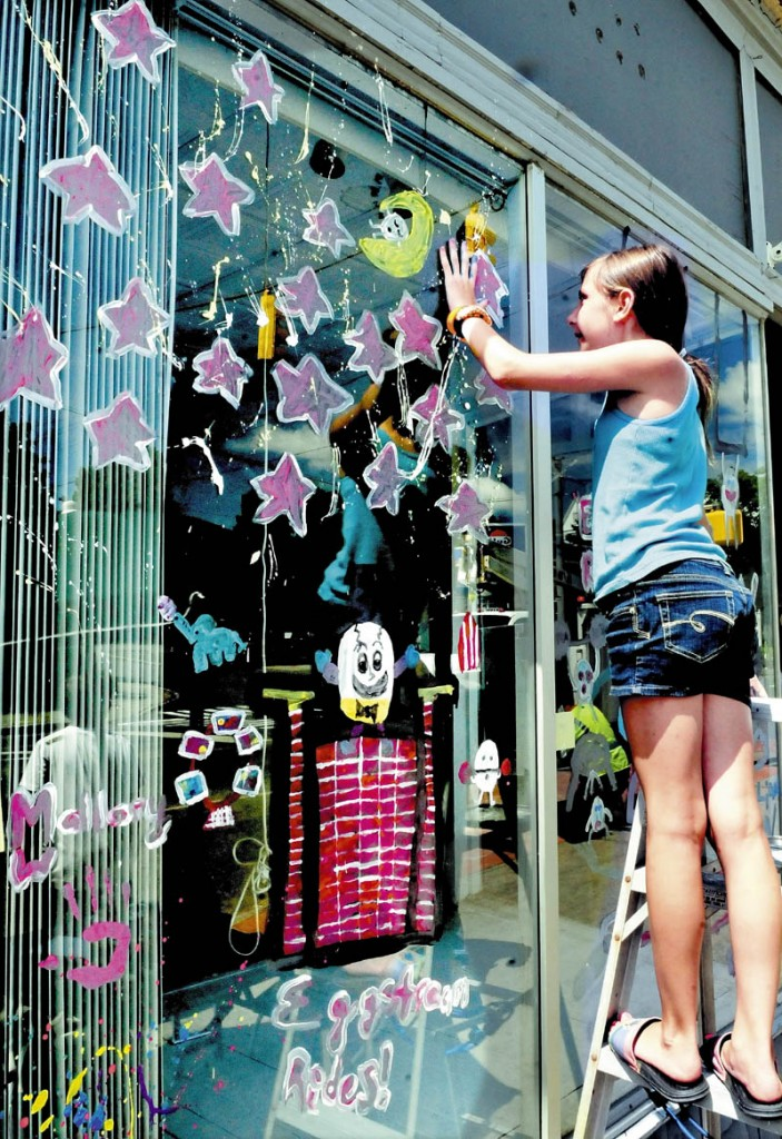 Mallory Whitney reaches up to place a hand print, while taking part in window painting on Main Street in Pittsfield on Thursday. The event was part of the week-long Central Maine Egg Festival.