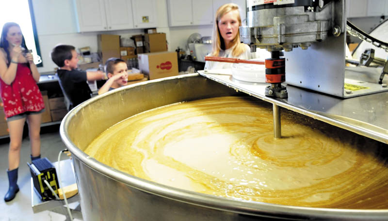Sophie Lindsay explains the process of preparing a huge container of honey for packaging at Swan's Honey in Albion during Maine Open Farm Day on Sunday, as from left, an unidentified girl, Alex Smith, and his brother, Ben, sample honey-topped ice cream. Farms statewide opened up their operations Sunday to visitors to learn about agriculture.
