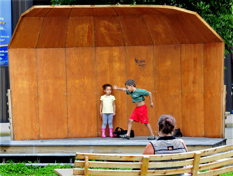 Davontay Gorham-Roy gets ready to do a cartwheel as his sister, Malia, waits her turn to perform on the stage in the Concourse in Waterville on Wednesday. Watching on a park bench is their mother, Natalie Roy.