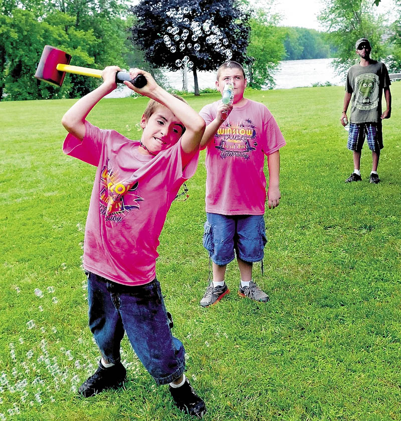 Hunter Desveaux swings a hammer to ring the bell on a game, as Gage Vaughan provides the bubbles, at Fort Halifax during the Winslow Family Fourth of July celebration on Monday. Live bands provided music and folks enjoyed a bean supper meal all day.