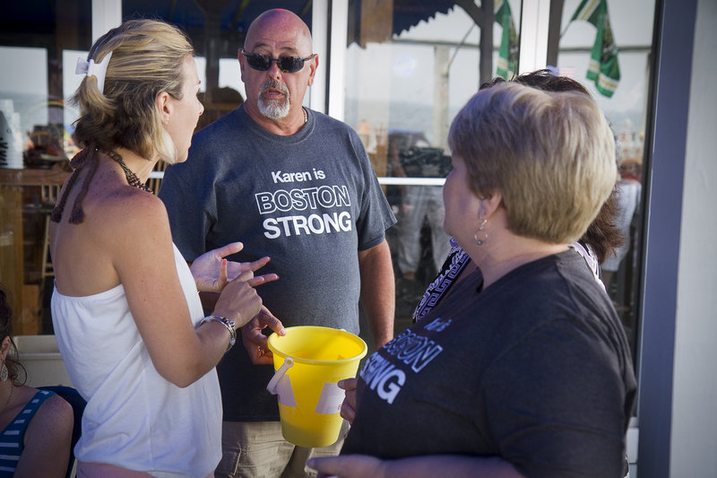 Event organizer Mal Mango of Old Orchard Beach coordinates a 50/50 ticket sale with Heather Dyer and Cheryl Engelhardt during a fundraiser Sunday at The Brunswick to help build a handicapped-accesible home for Boston Marathon bombing victim Karen Rand.