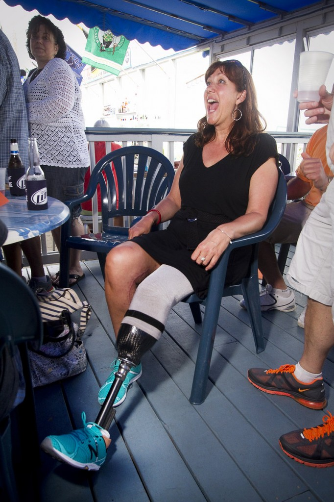 Boston Marathon bombing victim Karen Rand greets a friend Sunday at a fundraiser at The Brunswick.