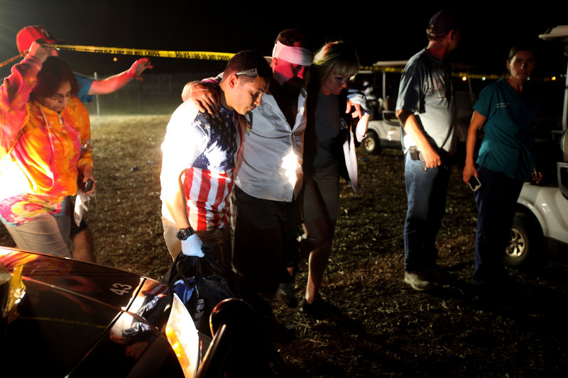 An injured man is assisted after a fireworks accident on Thursday in Simi Valley, Calif. At least 36 people were hurt.