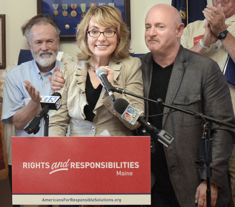 Gabrielle Giffords, center, receives a hug from her husband, Capt. Mark Kelly, right, after she spoke at Portland City Hall Saturday to promote federal gun-control legislation.