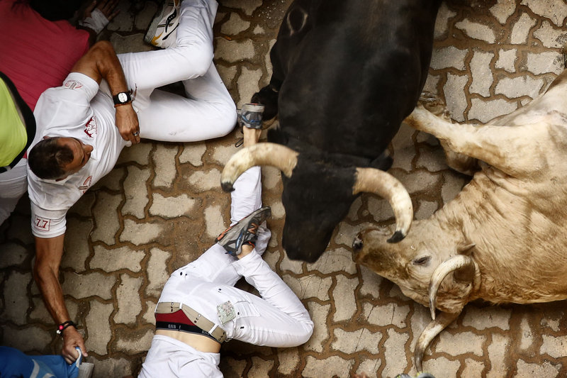Revelers and bulls lie on the ground during the running of the bulls in Pamplona, Spain, on Saturday.