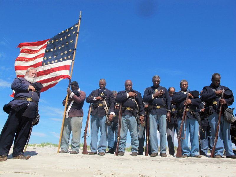 "Re-enactors pray on the beach on Morris Island in Charleston, S.C., in a ceremony honoring the 54th Massachusetts Volunteer Infantry, the black Union unit that attacked Confederate Battery Wagner, in a fight recounted in the film ""Glory."""