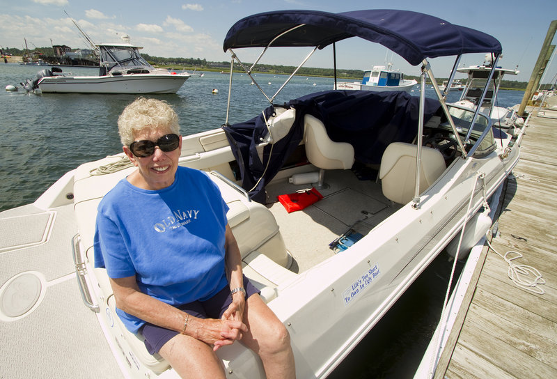 """Shirley Polinger of Wells sits on her boat Monday in Wells Harbor, where it was towed after becoming disabled Saturday off the coast. She said when a boater came to her aid, """"I was looking at the front of his boat and I saw 'Fidelity IV.' I said, 'Oh my God, it's Bush's boat.'"""""""