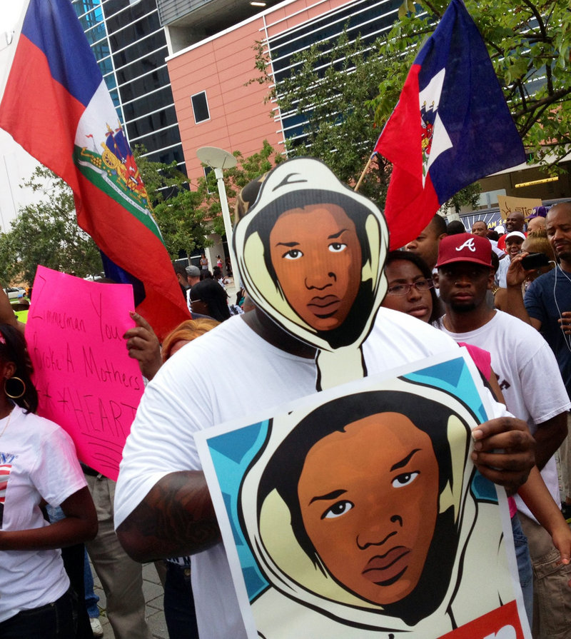 "Aqua Etefia holds signs during a ""Justice for Trayvon"" rally in Miami on Saturday. The Rev. Al Sharpton's National Action Network organized rallies nationwide to press for federal civil rights charges against George Zimmerman."