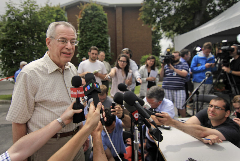 "Ed Burkhardt, chairman of the Montreal, Maine & Atlantic Railway, is surrounded by media representatives after arriving in Lac-Megantic, Quebec, on July 10. Burkhardt, the head of the company whose oil-tanker train killed 47 people when it exploded in the small Quebec town, heard cries of ""murderer"" from furious town residents."