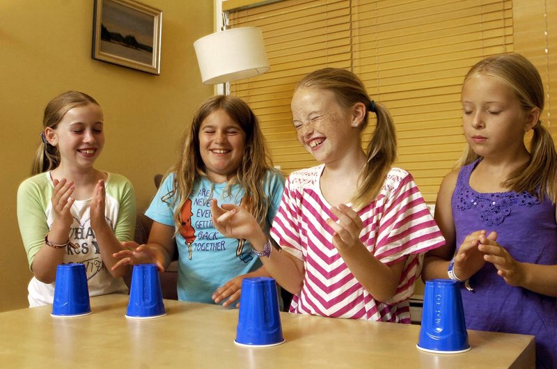 "From left to right, Hannah Johnson, Caitlin Guthrie, Katherine Concannon, and Tatum Strunk, all 10 years old and from Cape Elizabeth, share a laugh while practicing the ""Cups"" song at Johnson's house in Cape Elizabeth, Wednesday, July 24, 2013."