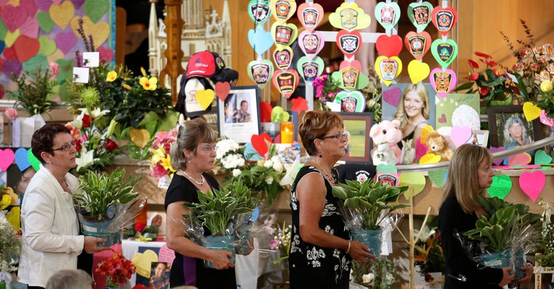 People proceed past a memorial during a ceremony at the Ste.-Agnes church in Lac Megantic, Quebec, on Saturday.