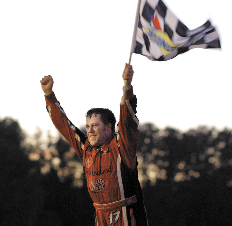 VICTORY LANE: Travis Benjamin raises the checkered flag after winning the 40th annual TD Bank 250 on Sunday at Oxford Plains Speedway in Oxford.