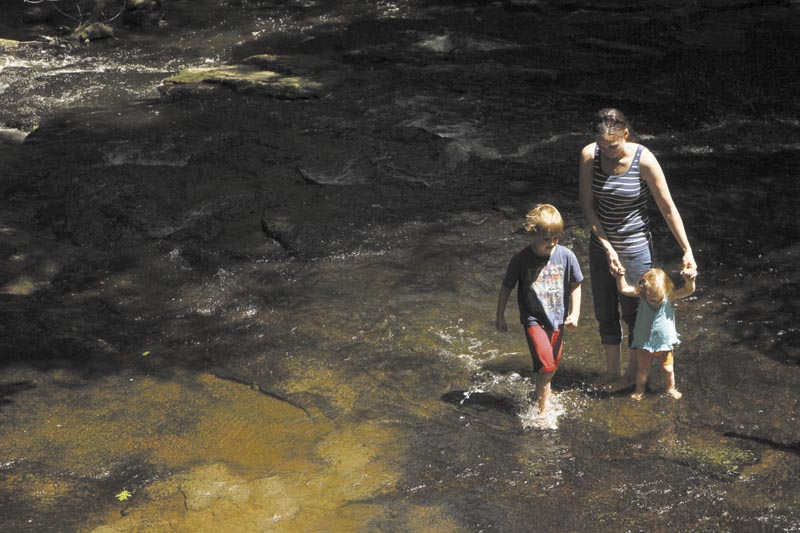 Lissa Niederer, of Augusta, her 20-month-old daughter, Kinsey, and 6-year-old son, Sam, cool their feet in a stream at Vaughan Woods in Hallowell on Friday. After a cloudy, wet start to the week, the weekend is expected to be hot, dry and perfect for outdoor activities.