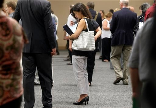In this July 15, 2013 file photo, a woman waits to talk with employers at a job fair for laid-off IBM workers in South Burlington, Vt. The government issues the jobs report for July on Friday, Aug. 2, 2013.