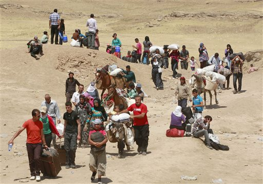 Syrian refugees cross into Iraq at the Peshkhabour border point in Dahuk, 260 miles northwest of Baghdad, Iraq, on Tuesday.
