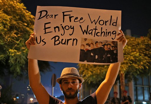 A Syrian man who lives in Beirut holds up a placard Wednesday in front of the United Nations headquarters during a vigil for the victims of the alleged chemical weapons attack in the suburbs of Damascus.