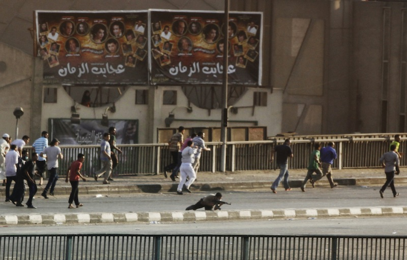 A man, center, holding a gun takes his position while having gunfire with other civilians in Cairo, Egypt, Friday, Aug. 16, 2013. Gunfire rang out over a main Cairo overpass and police fired tear gas as clashes broke out after tens of thousands of Muslim Brotherhood supporters took to the streets Friday across Egypt in defiance of a military-imposed state of emergency following the country's bloodshed earlier this week. (AP Photo/Manoocher Deghati)