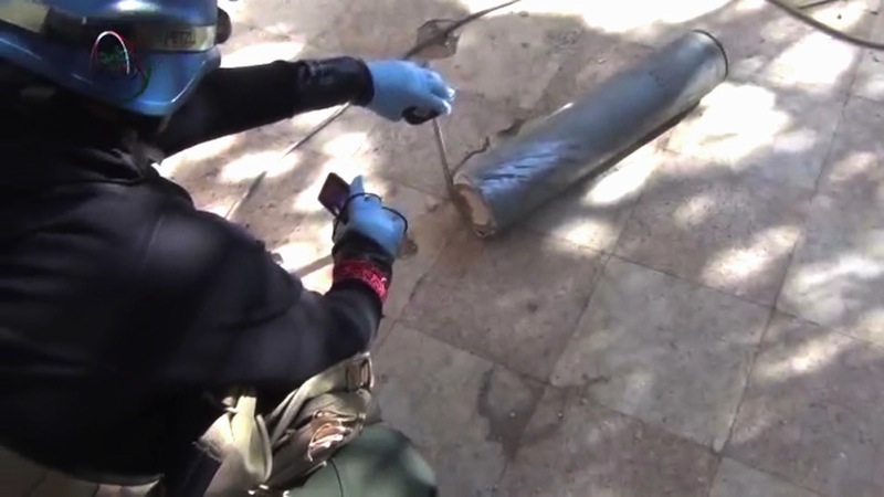 In this image taken from amateur video posted online, appearing to show a presumed UN staff member measuring and photographing a canister in the suburb of Moadamiyeh in Damascus, Syria, Monday Aug. 26, 2013, the suburb of Damascus where the Syrian regime allegedly used deadly chemical weapons. AP could not verify the authenticity of the video, but it is consistent with Associated Press reports. U.N. experts collected samples and testimony from Syrian doctors and victims of an alleged chemical weapons attack on Monday following a treacherous journey through government and rebel-held territory during which their convoy was struck by snipers. (AP Photo/MEDIA OFFICE OF MOADAMIYEH)