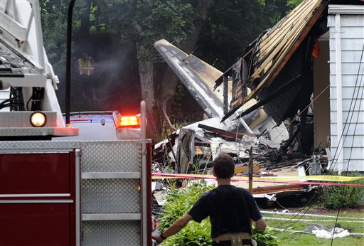 A firefighter surveys the scene of a small plane crash Friday in East Haven, Conn. The multi-engine, propeller-driven plane plunged into a working-class suburban neighborhood near Tweed New Haven Airport, on Friday.