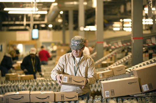 An Amazon employee grabs boxes off a conveyor to load a truck at the company's Fernley, Nev., warehouse.