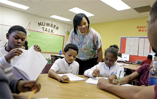 In this April 18 file photo, Burgess-Peterson Elementary School principal Robin Robbins, center, meets with students during an after-school study program in Atlanta, in preparation for state standardized testing, soon to begin. A new poll from the Associated Press-NORC Center for Public Affairs Research finds parents of school-age children view standardized tests as a useful way to track student progress and school quality.