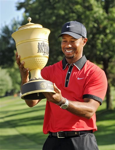 Tiger Woods holds the trophy after winning the Bridgestone Invitational on Sunday at Firestone Country Club in Akron, Ohio. Woods' 15-under par won by seven shots.
