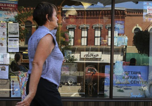 A shopper strolls past a storefront in downtown Ottawa, Ill., recently. Although consumers are more confident about the future, their assessment of the current economy dipped slightly in August.