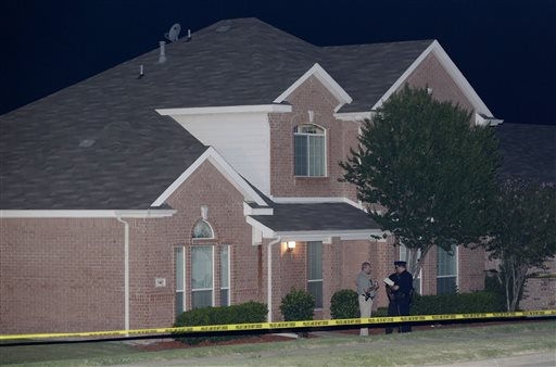 Law enforcement officers confer early Thursday morning outside the house where a fatal shooting took place in DeSoto, Texas.