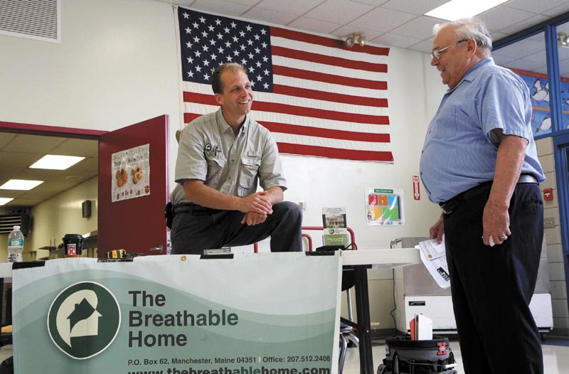Bo Jespersen, owner of The Breathable Home in Manchester, chats with Allan Laney of Norridgewock, right, at a free energy exposition at Madison Area Memorial High School today. Jespersen's business specializes in energy retrofits and energy audits.