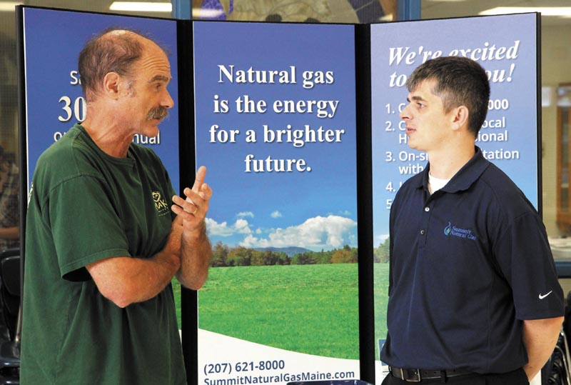 Ernie Hilton, left, of Starks, chats with Summit Natural Gas sales representative Ryan Wheaton at a free energy exposition at Madison Area Memorial High School today.