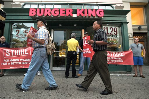 Protesters display placards outside a Burger King fast-food restaurant in Boston on Thursday. The protest was one of several planned in Boston.