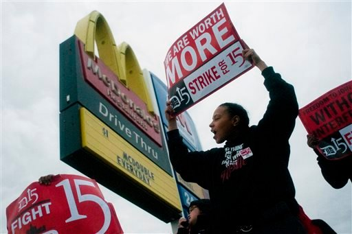 "Fast-food worker Michelle Osborn, 23, of Flint shouts out chants as she and a few dozen others strike outside of McDonald's on Wednesday, July 31, 2013 in Flint. Some fast food restaurant workers have walked off the job in the Detroit area as part of an effort to push for higher wages. Organizers say they began the walkout at restaurants in Lincoln Park and Southfield on Tuesday night. Workers in Flint hit the street Wednesday outside a McDonald's, saying they want wages ""super-sized."" Workers want $15 and hour, better working conditions and the right to unionize. The restaurant industry says higher wages would hurt job creation. The actions follow strikes this week in other parts of the country. (AP Photo/The Flint Journal, Jake May)"