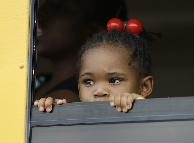 A child peers out the window of a school bus as busses arrive with students after an incident at Ronald McNair Discovery Learning Academy, Tuesday, Aug. 20, 2013 in Decatur, Ga. Superintendent Michael Thurmond says all students at Ronald E. McNair Discovery Learning Academy in Decatur east of Atlanta are accounted for and safe Tuesday and that he is not aware of any injuries. (AP Photo/John Bazemore)