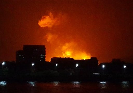 The night sky is lit up as a fire burns aboard INS Sindhurakshak, an Indian Navy kilo class submarine, early Wednesday in Mumbai, India. The submarine caught fire after an explosion aboard the vessel, and sank.