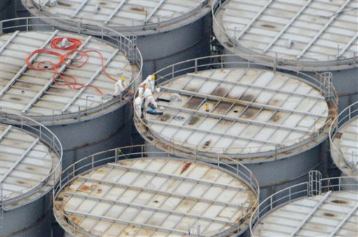 In this Tuesday aerial photo, workers stand on one of the hundreds of steel storage tanks at Japan's crippled atomic power plant in Fukushima prefecture, northern Japan. The operator of the plant says about 80,000 gallons of contaminated water have leaked from one of the tanks.