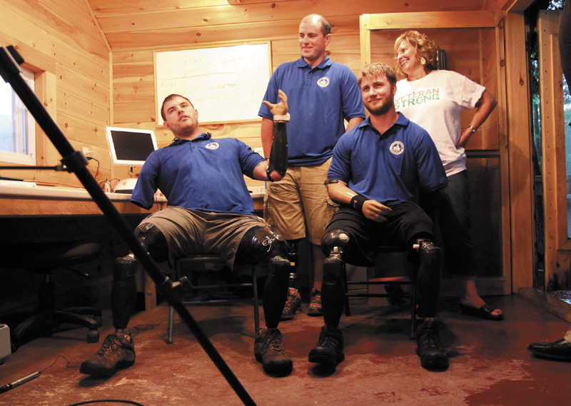 """Quadruple amputee Travis Mills, left, talks to reporters with fellow wounded veterans Taylor Morris, right, and Drew Mullee, top, as Maine's First Lady Ann LePage looks on at Camp Kennebec in Belgrade on Wednesday night. This week is """"Founder's Week"""" at the Travis Mills Project National Veterans' Family Center at the camp located on the shores of Salmon Lake."""
