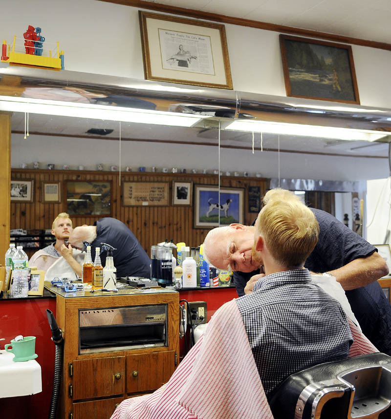 Gil Taylor gets his beard trimmed Thursday from barber Roland Marquis at Dom's Barbershop in Hallowell.