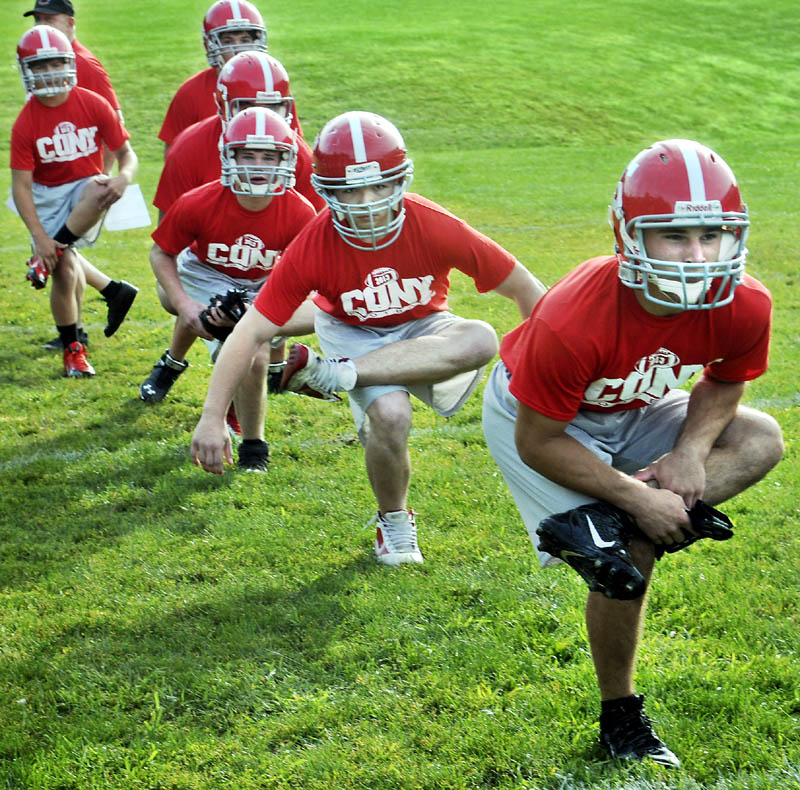 IT BEGINS: Cony High School football player John Bennett, right, leads his squad in a stretch during the first morning of football practice Monday at Cony High School in Augusta.