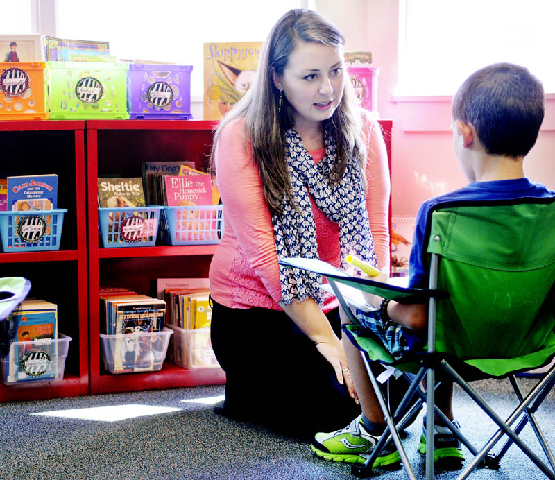 Wayne Elementary School teacher Danielle Nason helps student Elliott Desjardins with a lesson Wednesday on her first day as a teacher.