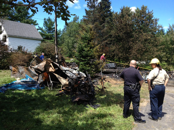 Investigators from the Office of the State Fire Marshal and Richmond Police examine the remnants of a mobile home that burned Sunday night on Kimball Street in Richmond.