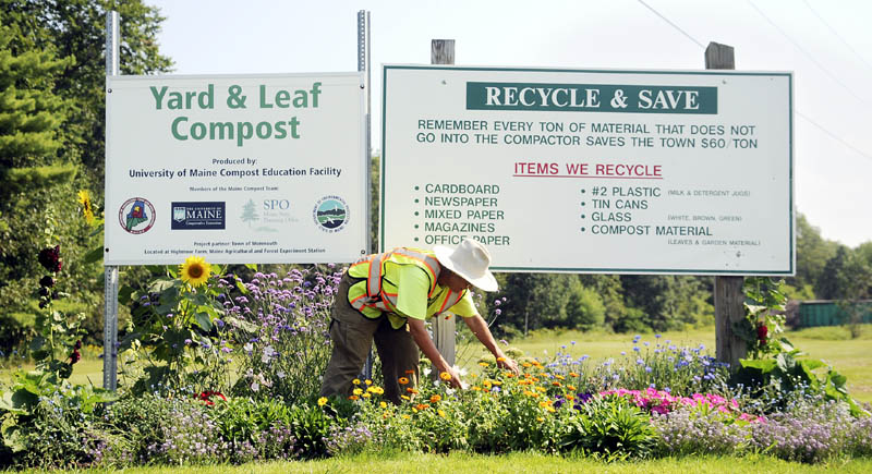 "Trudie Lee picks deadhead flowers Thursday beneath a sign at the Monmouth Transfer Station. The part-time employee of the disposal and recycling site has cultivated garden beds around signs at the entrance and in beds at the station, according to Herb Whittier, who oversees the facility. ""It's the best-looking transfer station in the state,"" he boasted."