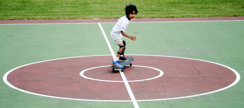 """Aryan Das, 6, skates across center court today at Williams Playground in Augusta. The Augusta resident graduated from a scooter this week to roll without handle bars on the skateboard, according to his father, Anupam Das. """"I like it now,"""" the younger Das said."""