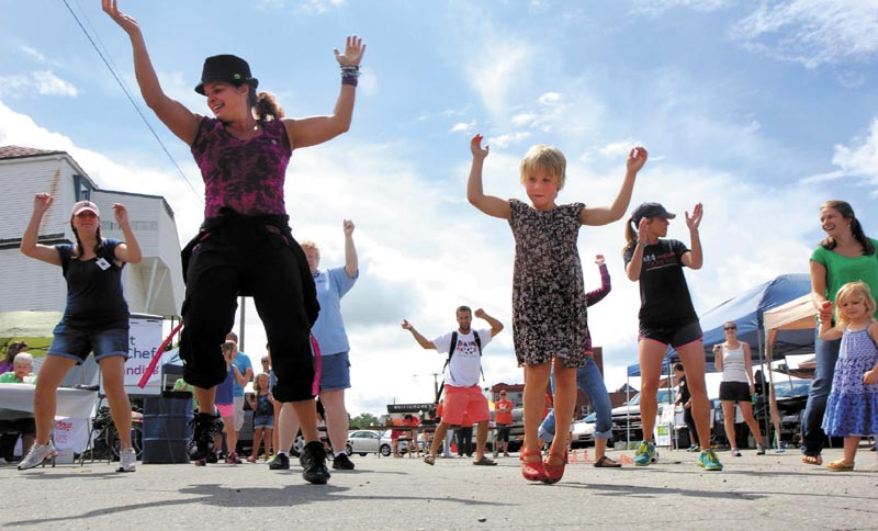 Natalie Cooke, 5, of Cornville, right, follows instructor Monica Gilbert Beach, of Fairfield, near left, during a Zumba session at Move More Kids Day at the Skowhegan River Fest today. The child-centered day included a handful of activities to promote healthy living and was sponsored by the New Balance Foundation and Greater Somerset Public Health Collaborative.