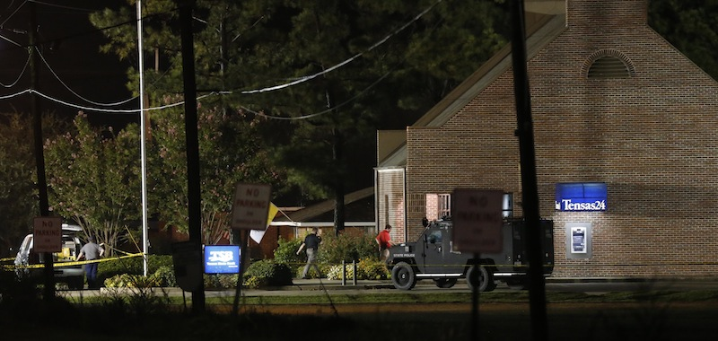 Investigators work throughout the early morning hours Wednesday, Aug. 14, 2013 at the Tensas State Bank branch in St. Joseph, La., where a gunman took three people hostage Tuesday. A second hostage shot during the standoff died Thursday at a hospital. (AP Photo/Rogelio V. Solis)