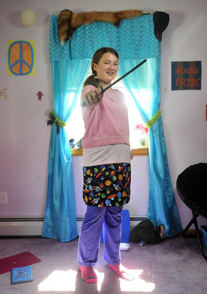 Bryn Mayo, waves her wand as she stands in her Fairfield home bedroom dressed as her favorite Harry Potter character, Luna, on Wednesday. Mayo plans to attend a Harry Potter party at the Lawrence Library in Fairfield on Thursday.